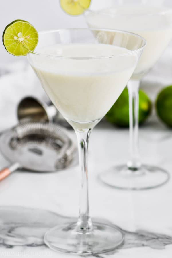 martini glass filled with white key lime martini recipe and garnished with a key lime slice, another glass, a cocktail strainer and limes in the background