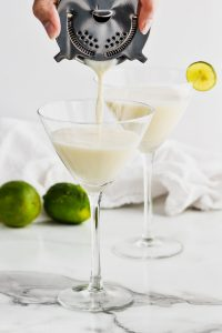 cocktail strainer pouring a white key lime martini recipe into a martini glass, another glass in the background that is full and garnished with a key lime wedge