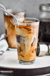 two tall tumblers with ice, iced coffee, and cream swirling in them with metal straws