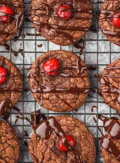 a chocolate covered cherry cookie that has been drizzled with ganache on a wire rack next to other cookies