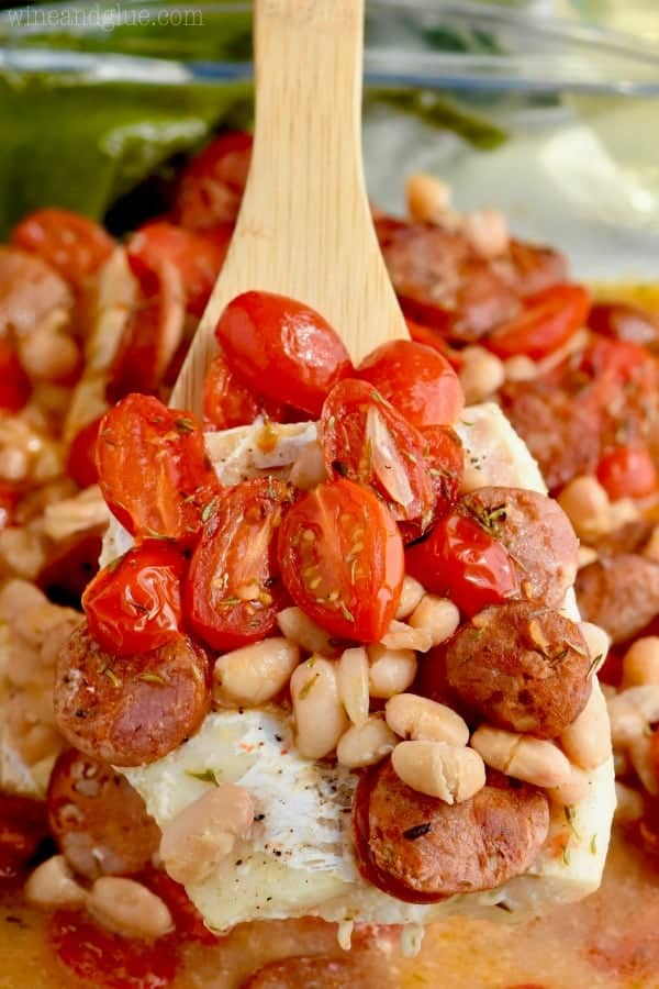 A wooden spoon is filled with roasted tomatoes, pinto beans, sausages, and fish.