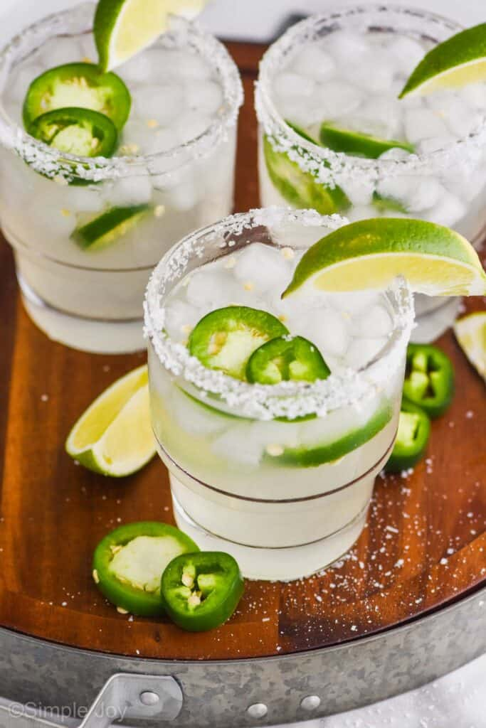 overhead of a wood tray with a metal rim that has three jalapeño margaritas in tumblers with salt rims, lime wedges, and fresh jalapeño slices