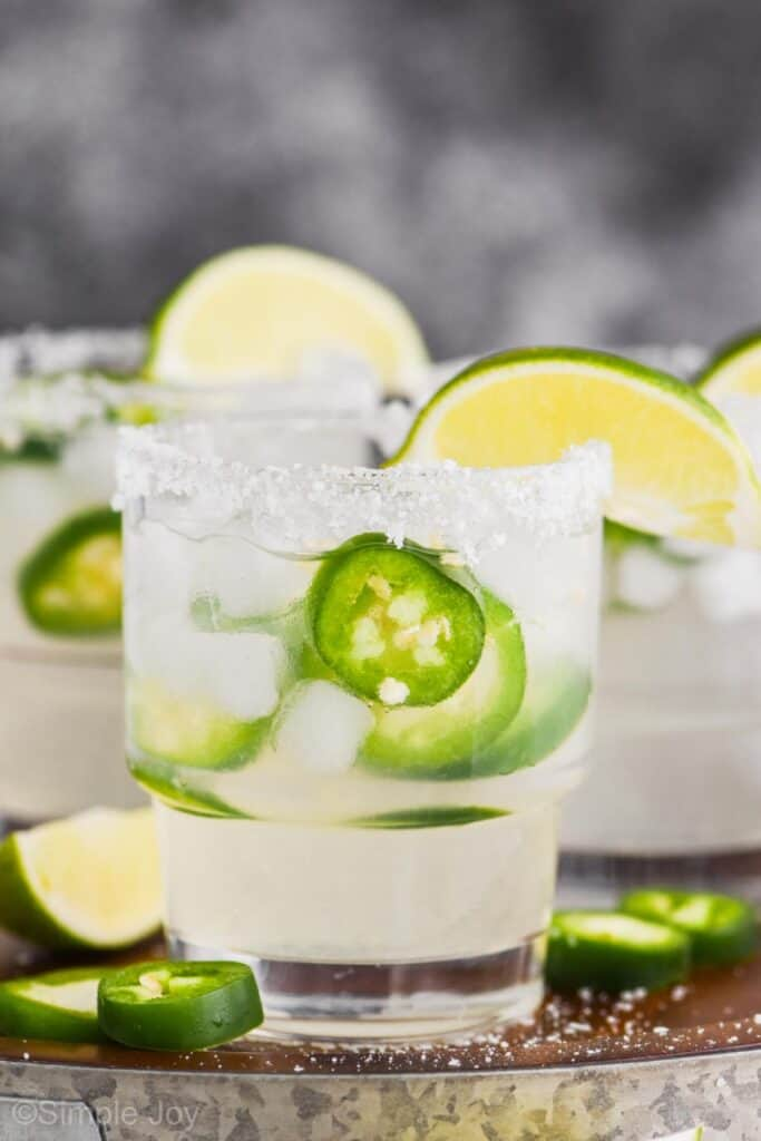close up picture of a tumbler lined with salt, garnished with a lime wedge filled with a jalapeño margarita that has fresh jalapeño slices
