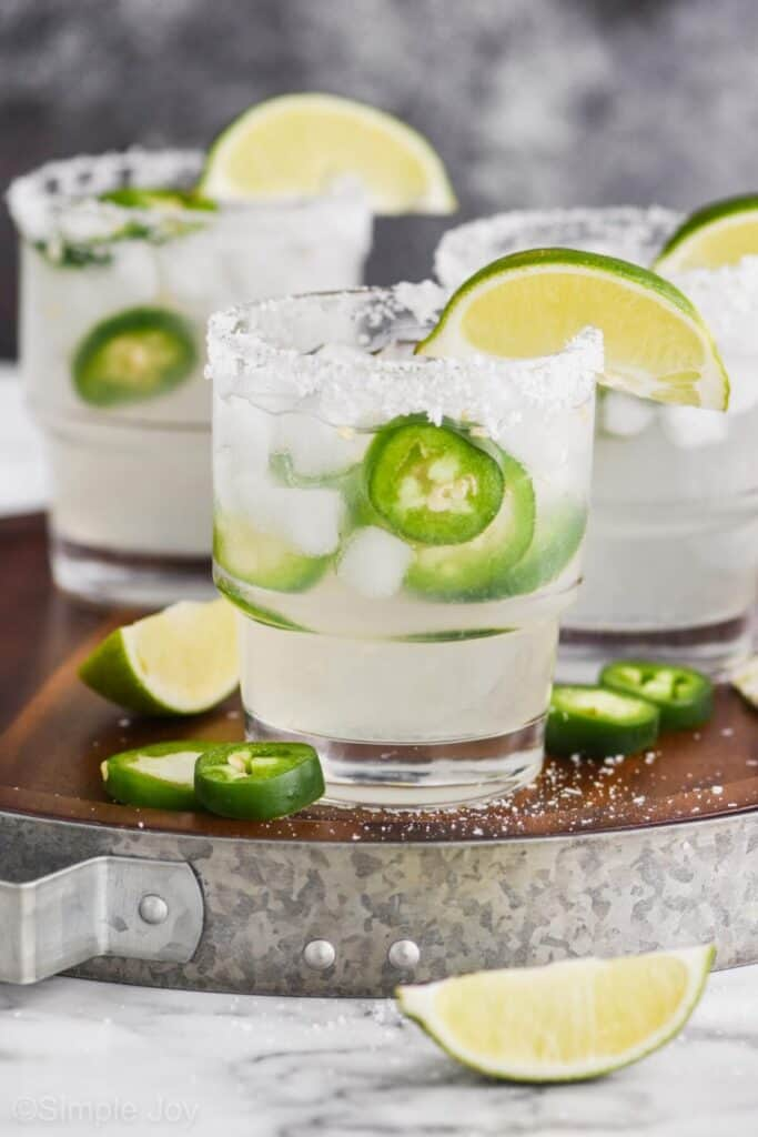pulled back look at three margarita glasses rimmed with salt, garnished with lime wedges and with fresh jalapeños and ice in them