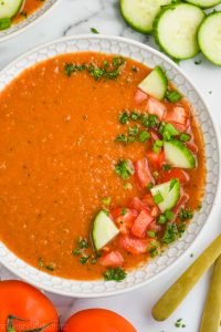 overhead view of a white bowl filled with gazpacho recipe and garnished with chopped fresh vegetables