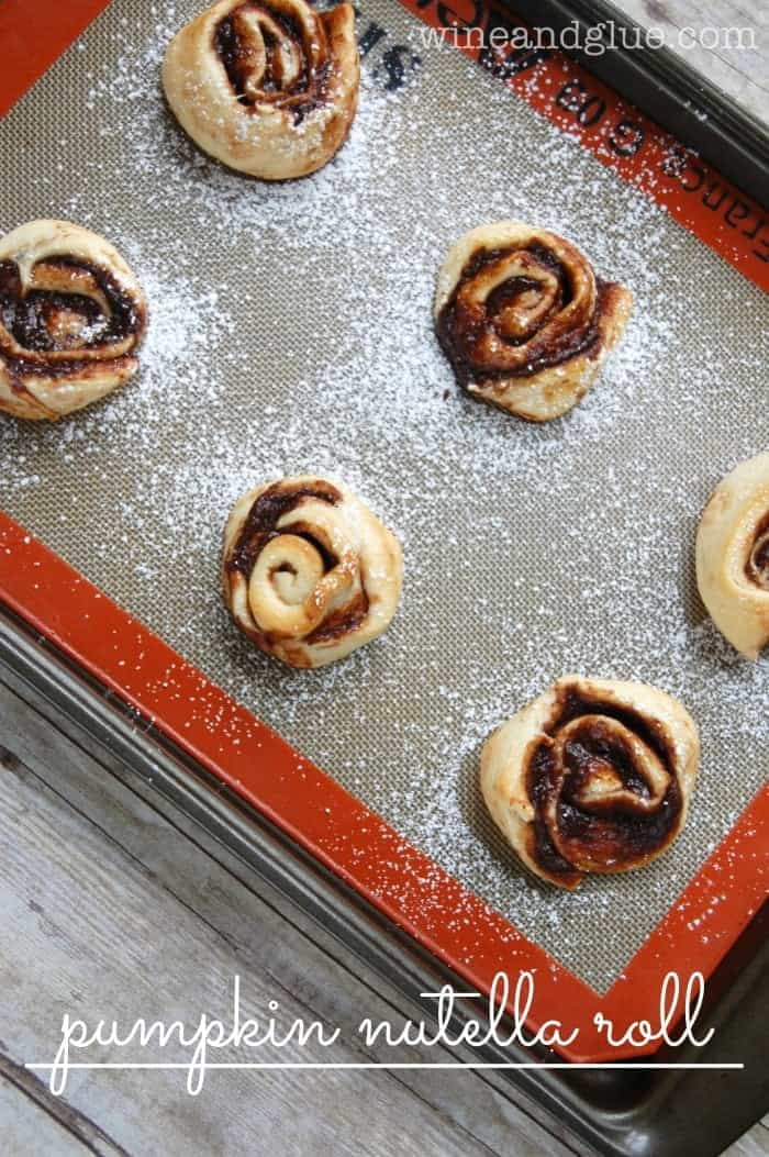 Pumpkin Nutella Rolls! The delicious flavors of pumpkin and Nutella swirled together in a delicious pinwheel. Super simple to make and incredibly delicious! via www.wineandglue.com