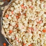 a large metal tray with parchment paper full of pumpkin spice white chocolate popcorn