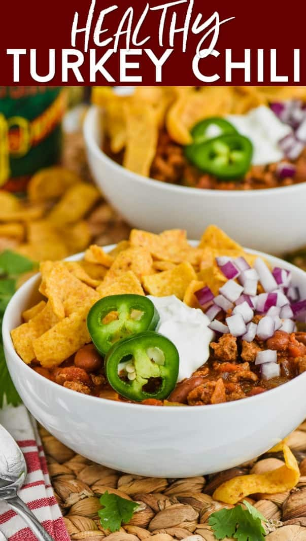 bowl of healthy turkey chili garnished with jalapeños, sour cream, chips and red onions