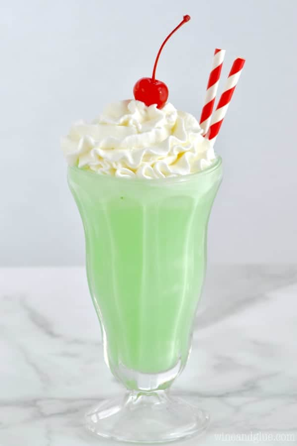 In a milkshake glass, the Copycat Shamrock Shake has a neon green color with whipped cream on top with a maraschino cherry.