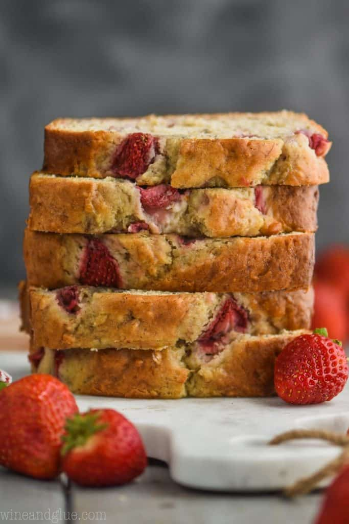 pieces of strawberry banana bread recipe stacked up on a marble cutting board against a dark background