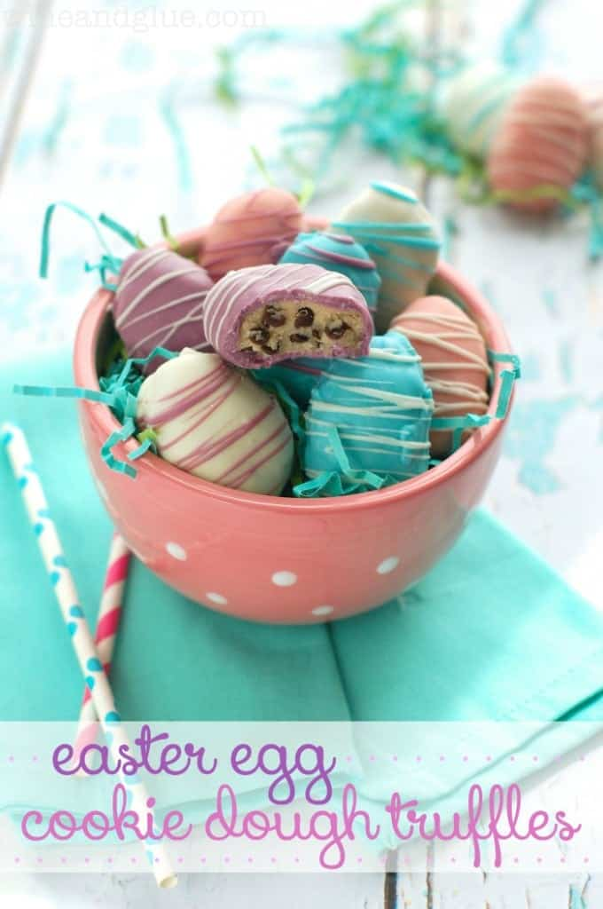 In a pink bowl, the Easter Egg Cookie Dough Truffles is covered with different colored chocolates (white, pink, purple, and blue) and drizzled with different colored stripes.