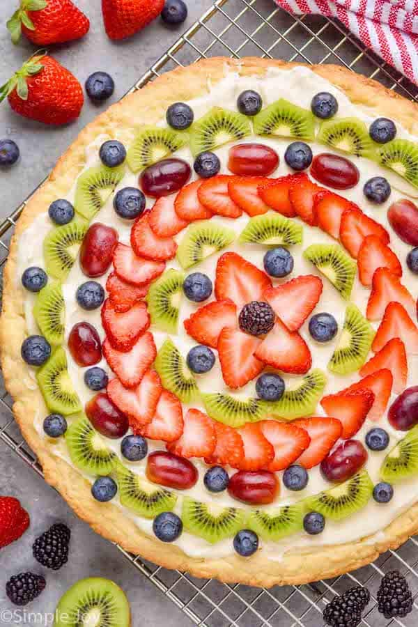 overhead view of a fruit pizza that is decorated with slices of fruit