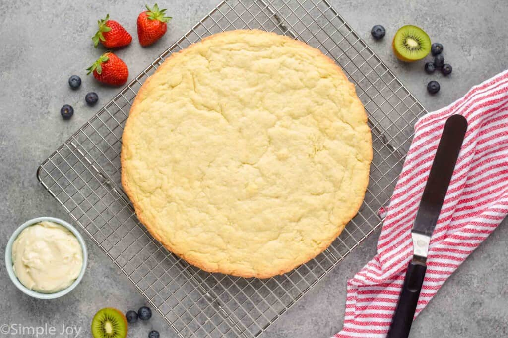 overhead view of a giant pizza sized sugar cookie on a cooling rack