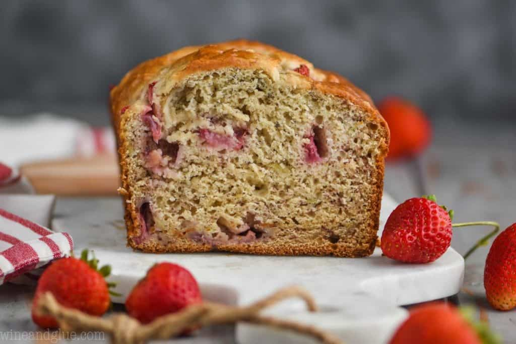 landscape photo of a loaf of strawberry banana bread cut in half, fresh strawberries visible in the bread, and fresh strawberries on the marble cutting board bread is sitting on