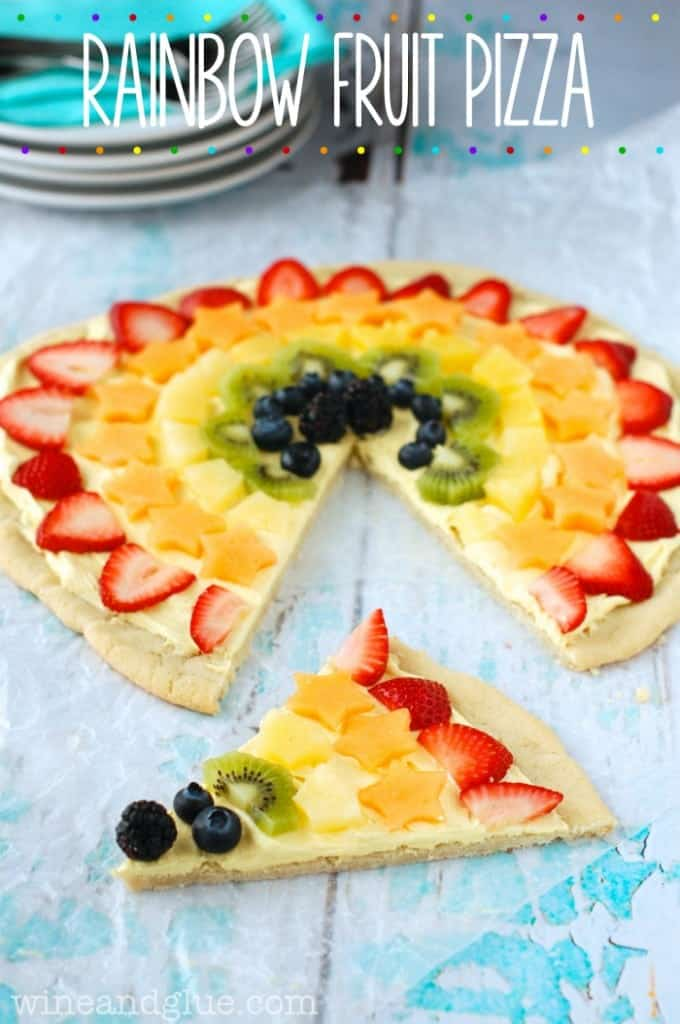 The Rainbow Fruit Pizza has a circular shape with a sugar cookie crust and cut strawberries, cantaloupe, pineapple, kiwi, blueberries, and blackberries.