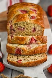 overhead view of strawberry banana bread sliced on a marble cutting board