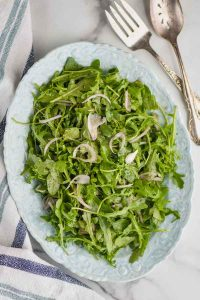 overhead view of an oval plate with an arugula salad on it