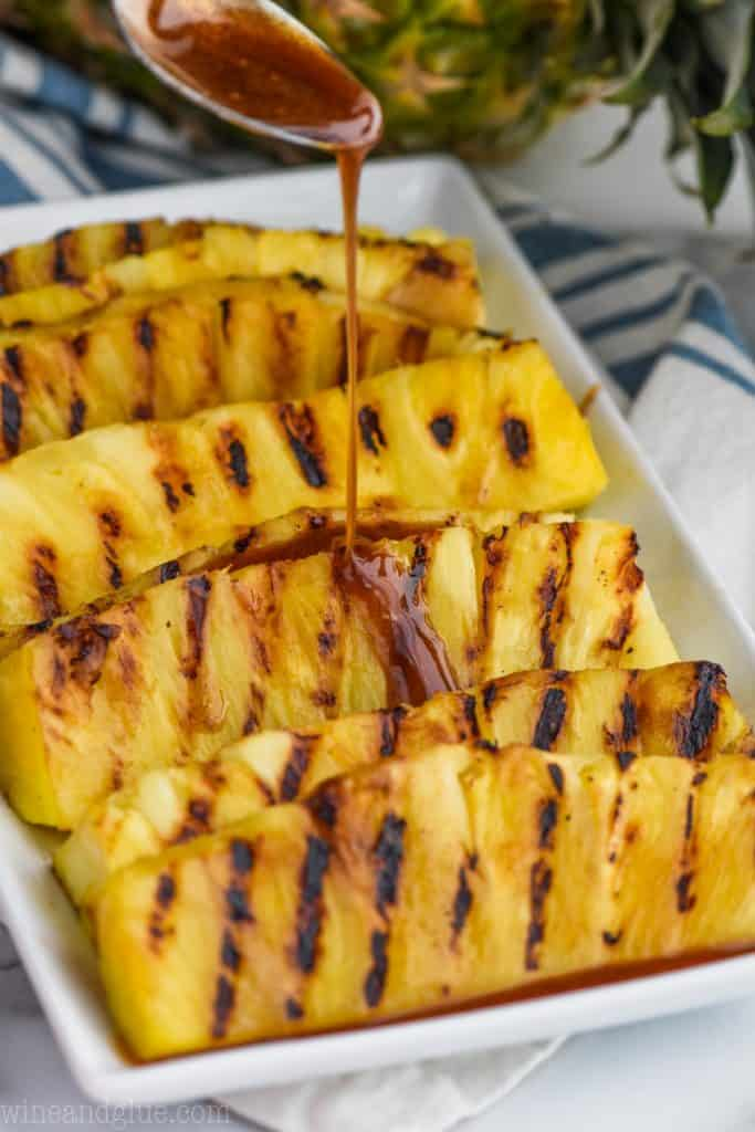 cinnamon honey drizzle being poured over a plate of grilled pineapple pieces