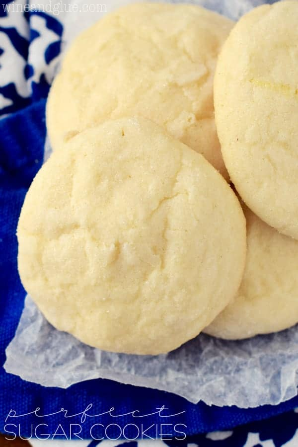 several sugar cookies piled on each other on wax paper which is on a blue cloth napkin