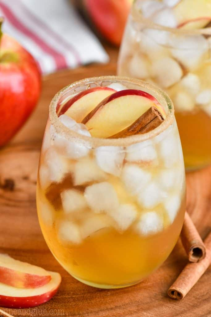 an apple cider margarita in a glass with ice and garnished with an apple