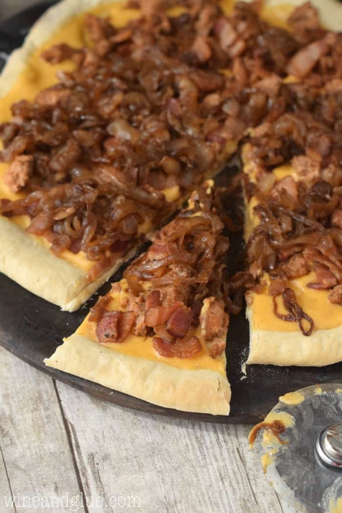 Delicious caramelized onions, spicy sausage, and bacon all over beer cheese sauce makes this serious pizza!