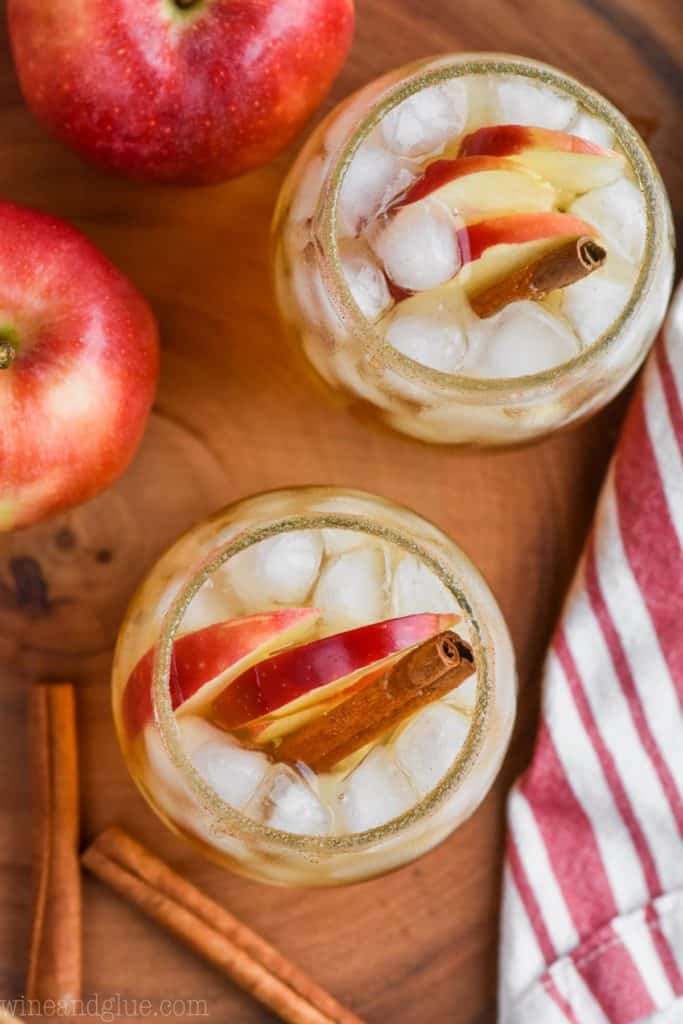 overhead view of two glasses of hard cider and tequila recipe in glasses with apples and cinnamon sticks