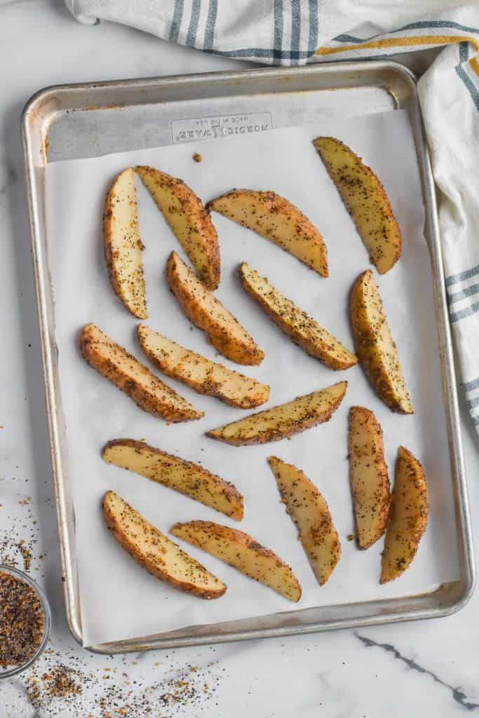 roasted potato wedges on a baking sheet