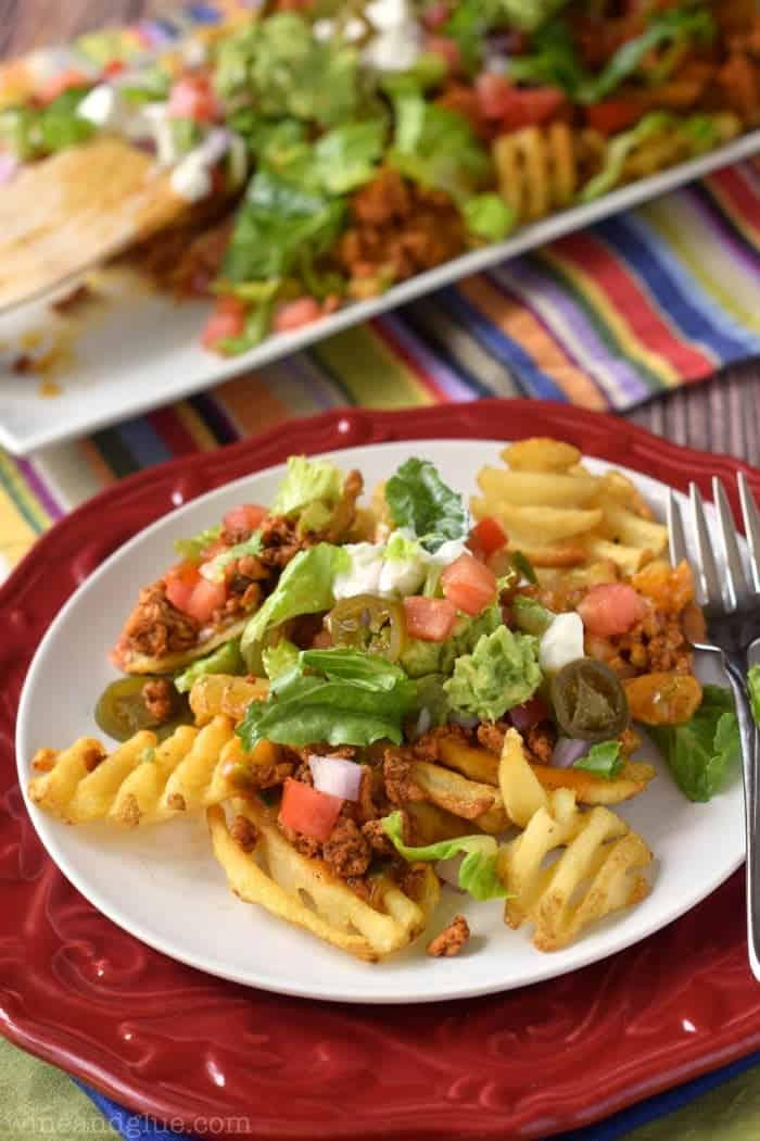 Delicious nachos made with lean meat, tons of veggies, and a homemade queso sauce, all over crispy waffle fries!