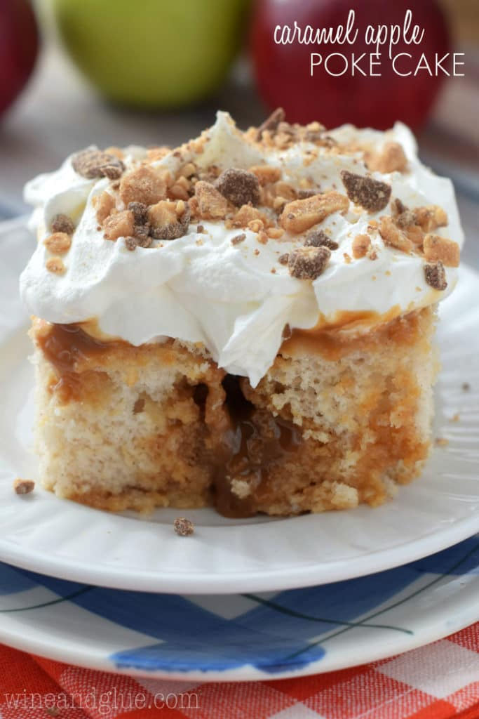 A slice of the Caramel Apple Poke Cake has caramel oozing out in the middle of the cake and topped with white frosting and broken up toffee bits.