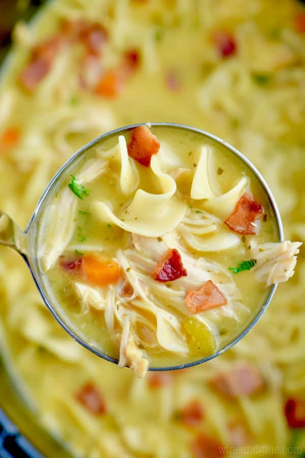 An overhead photo of a scoopful of the Crock Pot Chicken Bacon Ranch Soup showing the minced bacon, the noodles, carrots, shredded chicken, and the golden broth.