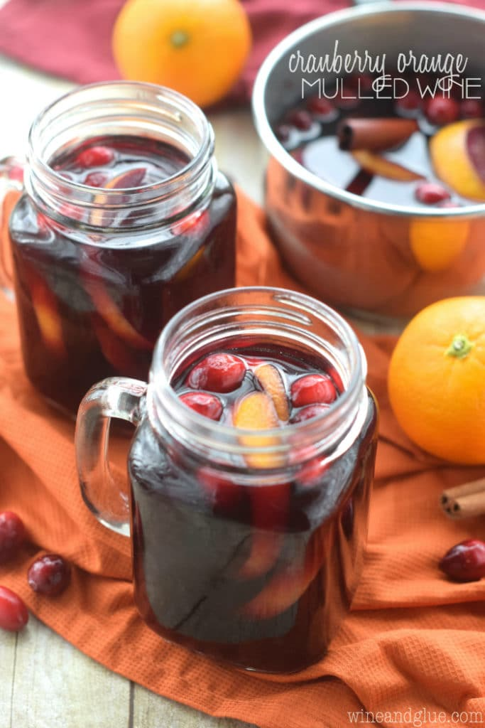 In mason jar glasses, the Cranberry Orange Mulled Wine has a dark maroon color with orange peels and cranberries.