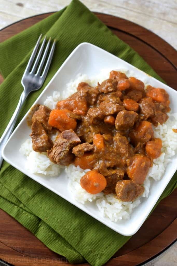 On a white plate, the Crockpot Beef Curry is on top of white rice.