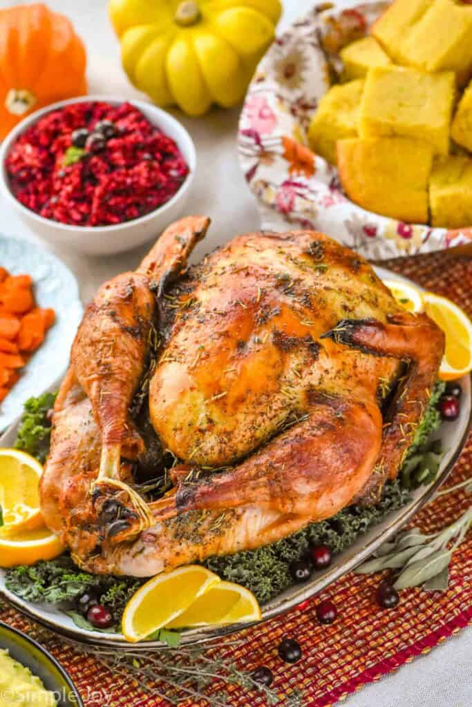 a thanksgiving turkey on a platter with greens, orange wedges, and cranberries