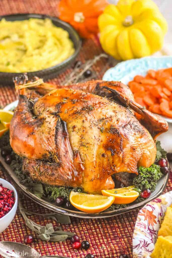 a roast turkey on a platter with greens, orange slices, fresh cranberries, surrounded by side dishes
