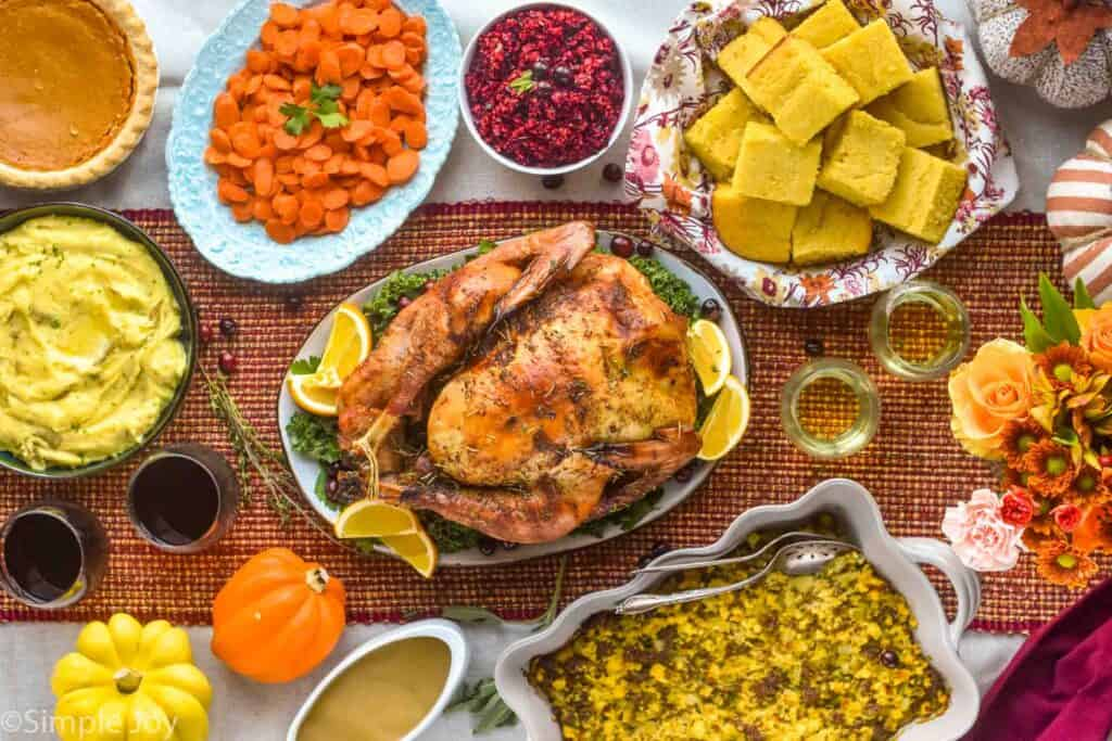 overhead view of a thanksgiving table, with a roast turkey and all the sides