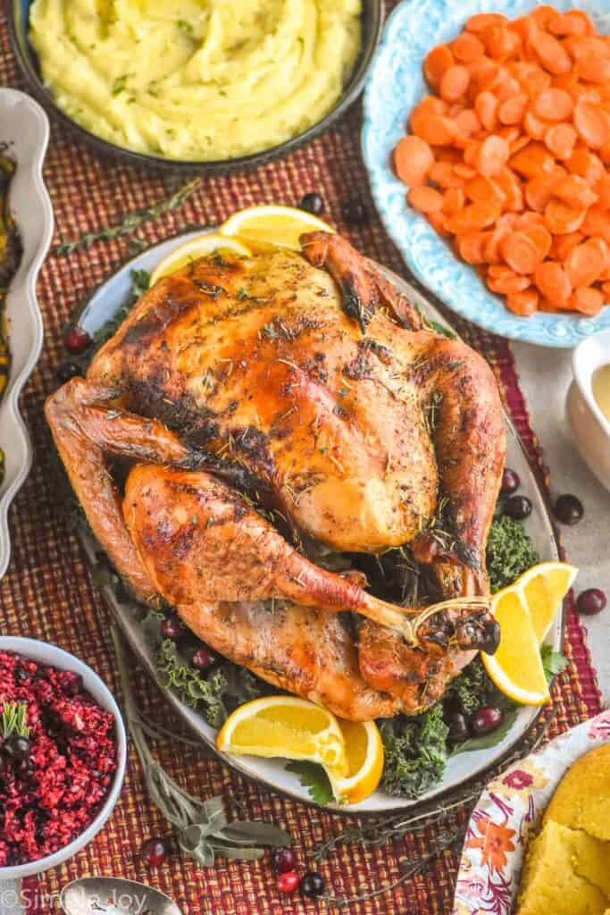 overhead view of a roast turkey on a platter surrounded by side dishes