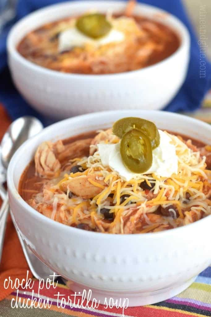 In a white bowl, the Crock Pot Chicken Tortilla Soup has a maroon brown color with shredded chicken and topped with shredded cheese, sour cream, and sliced jalapeños.