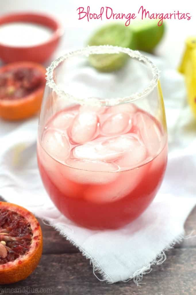 In a glass, the Blood Orange Margaritas has cubed ice in a dark magenta colored drink and rimmed with salt.