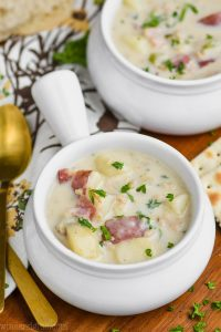 small white soup bowl full of new england clam chowder recipe and garnished with parsley