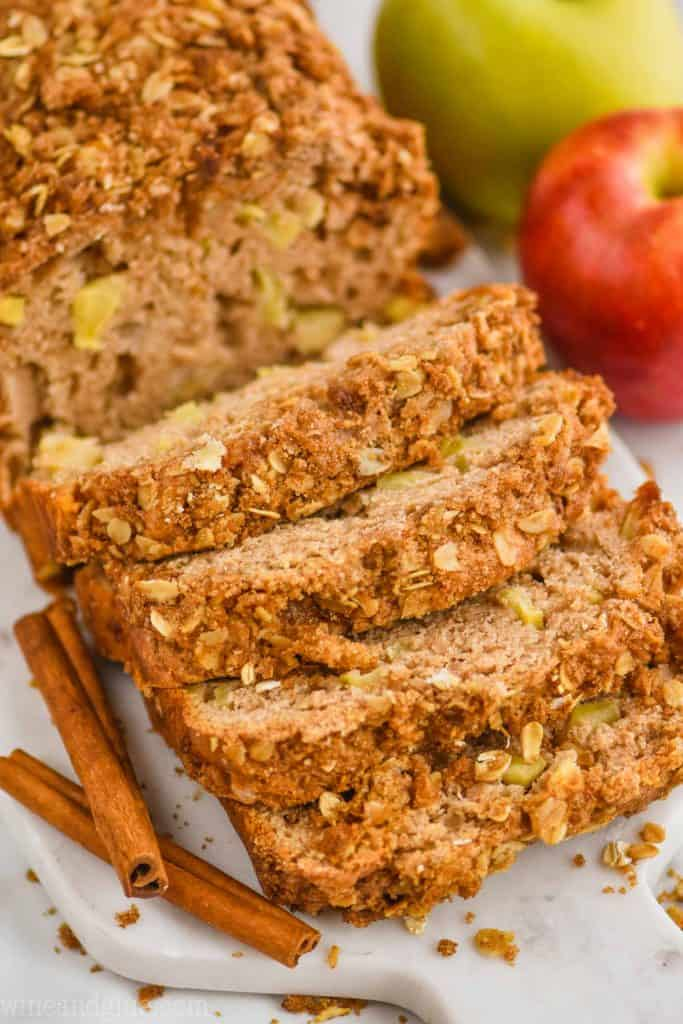 close up of cinnamon apple bread with streusel bread that has been sliced into on a marble cutting board with cinnamon sticks next to it and apples in the background