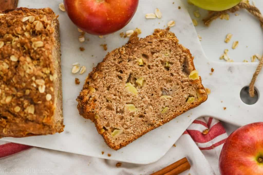 overhead view of a slice of easy apple bread recipe on a marble cutting board with oats around and fresh apples