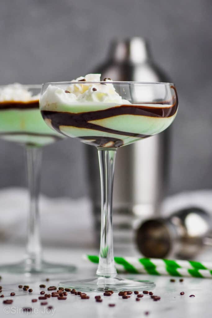 a tall coup glass lined with chocolate syrup filled with a green grasshopper cocktail and chocolate sprinkles around the base of the glass