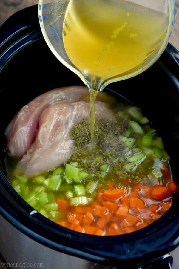 pouring chicken broth into a crock pot to chicken noodle soup