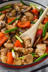 Serving spoon digging into a skillet of easy szechuan chicken
