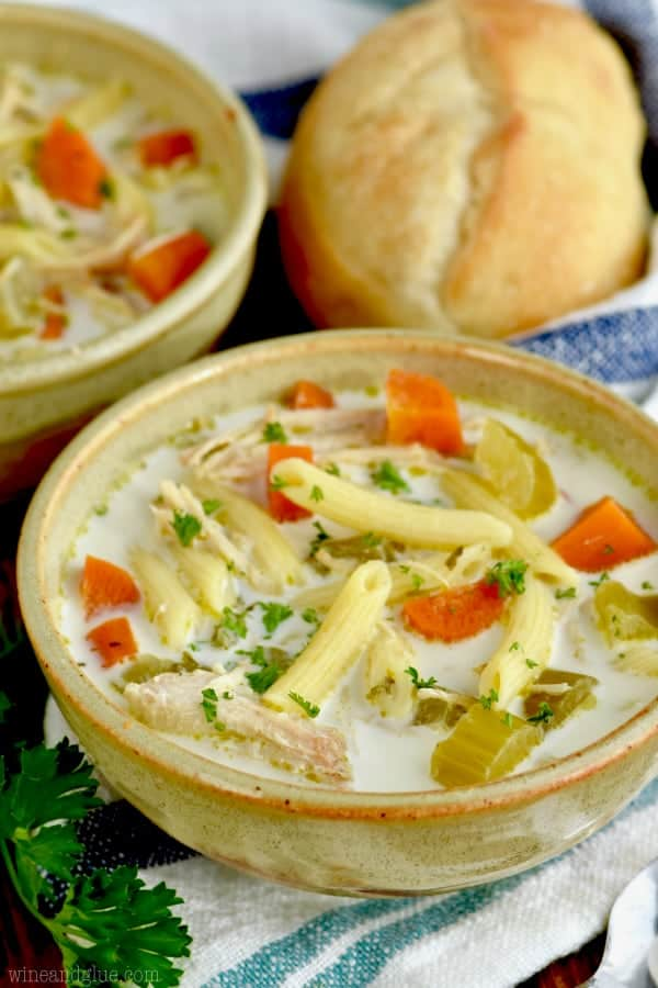 side view of a bowl of creamy slow cooker chicken noodle soup with penne noodles and fresh parsley