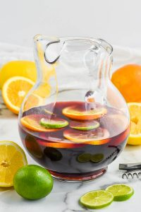 clear pitcher of the best red sangria recipe with lemons, limes, and oranges floating in it