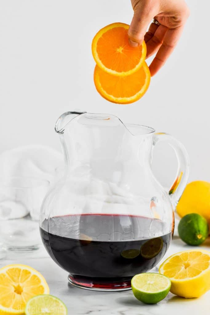 oranges being added to red wine to make red wine sangria