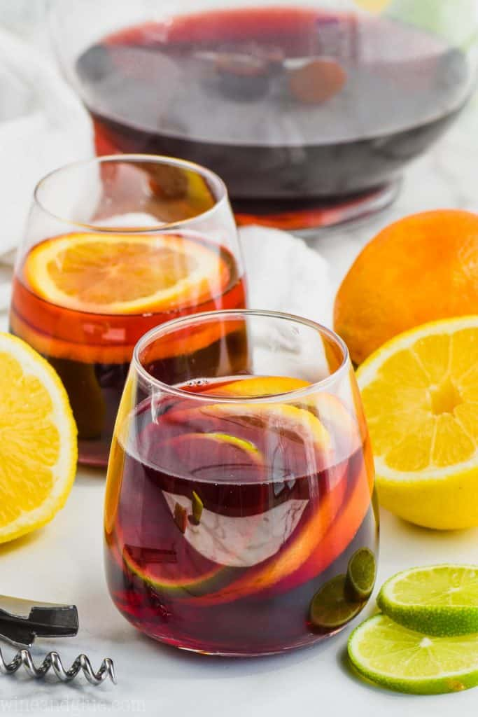 two glasses of red sangria recipe filled with slices of lemon, lime, and oranges
