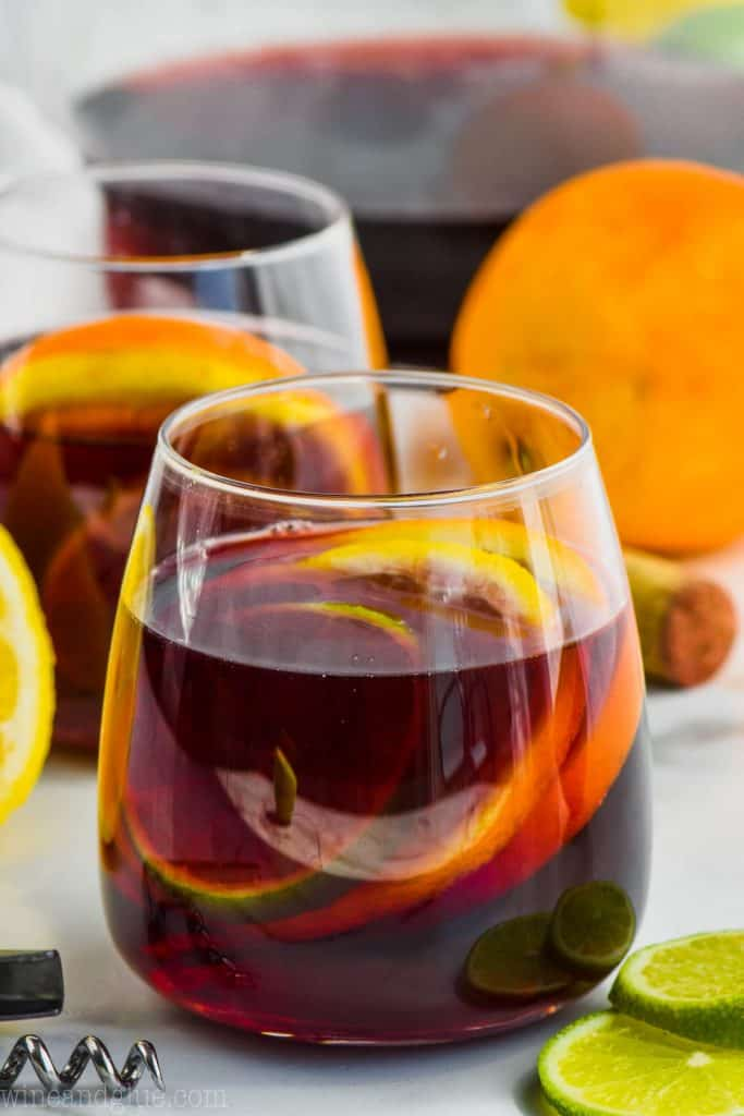 glass of red wine sangria filled with slices of lime, lemon, and orange with another glass in the background