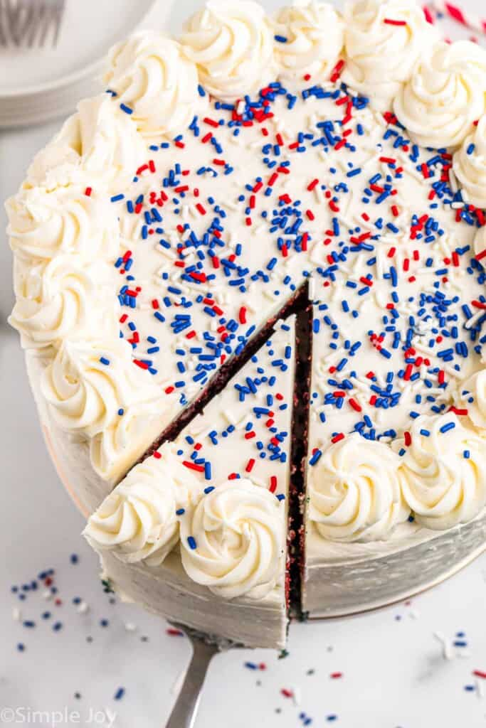 overhead photo of a white cake with red and blue sprinkles and a piece coming out